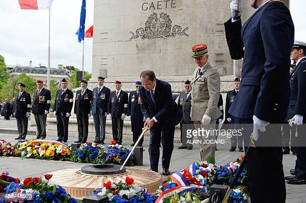 France's President Francois Hollande rekindles the flame after laying a wreath at the grave of the unknown soldier during a ceremony marking the 69th...