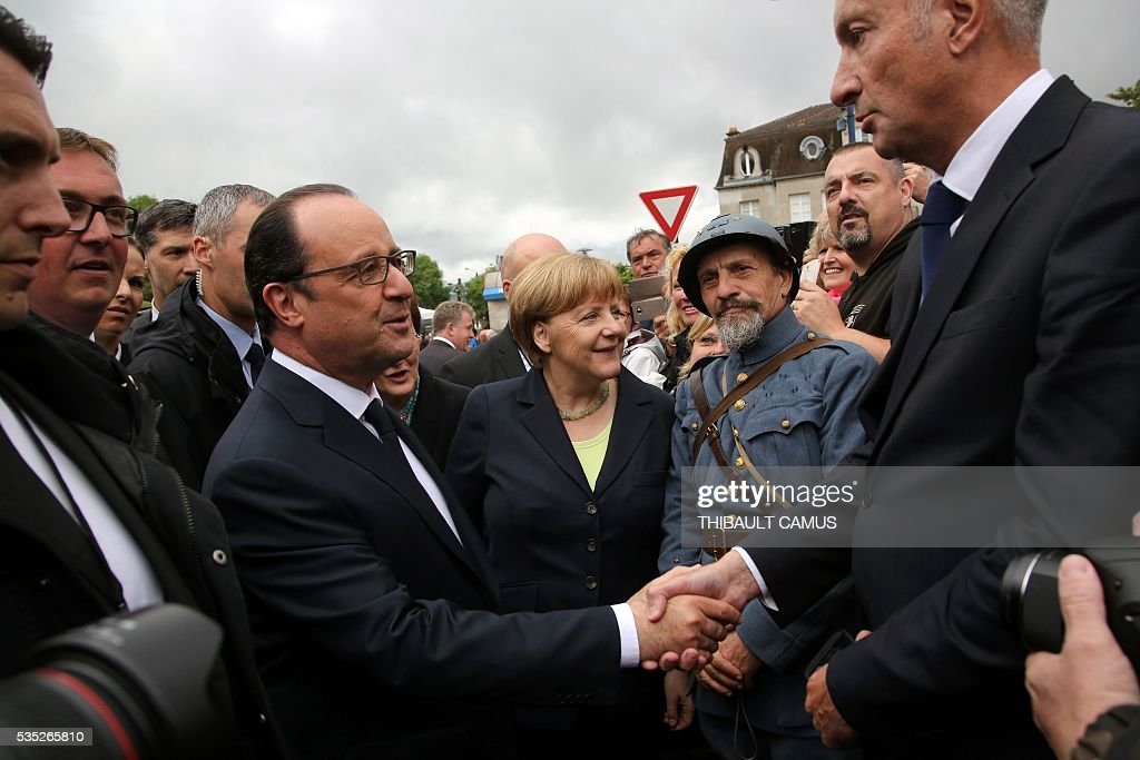 France's President Francois Hollande (L) salutes a man as German Chancellor Angela Merkel (C) stands by a history reenactor dressed as a World War I French soldier during a remembrance ceremony to mark the centenary of the battle of Verdun, in Verdun, on May 29, 2016. The battle of Verdun, in 1916, was one of the bloodiest episodes of World War I. The offensive which lasted 300 days claimed more than 300,000 lives. / AFP / POOL / Thibault Camus