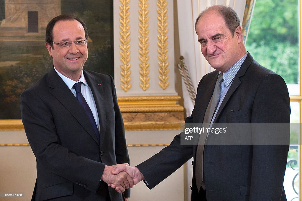 France's President Francois Hollande (L) shakes hand with French businessman and journalist Pierre Lescure after receiving a report about cultural politics in the digital period at the Elysee presidential Palace on May 13, 2013 in Paris.