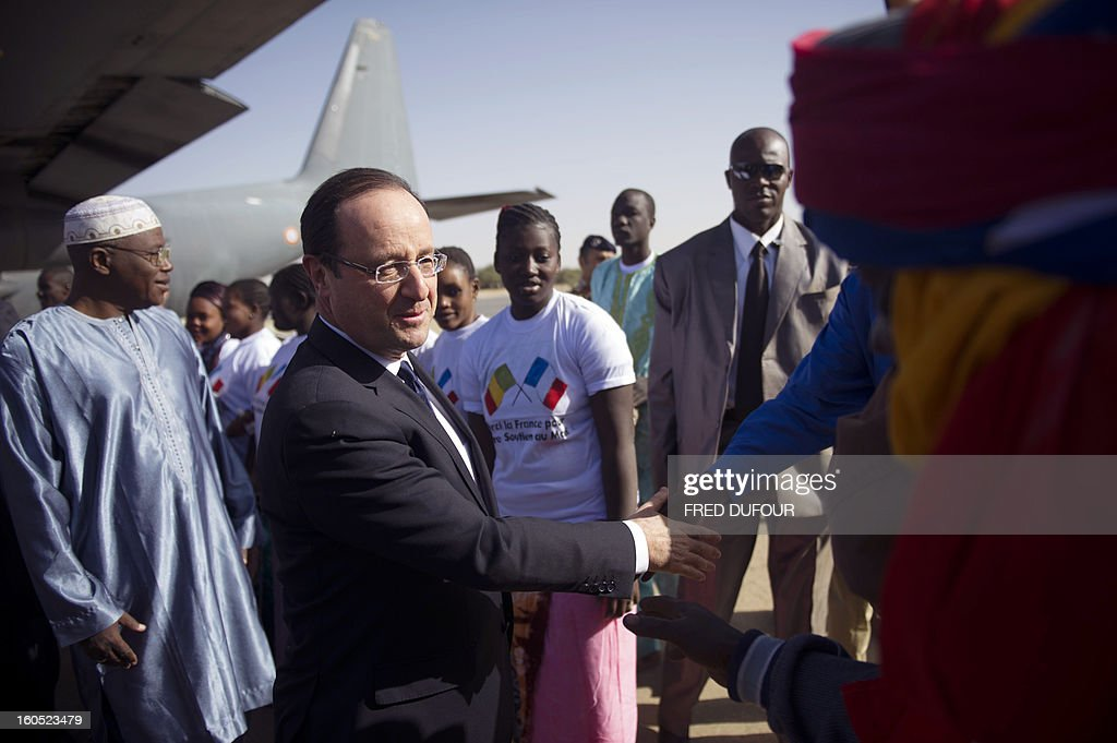 France's President Francois Hollande shakes hands as he arrives at the airport of Timbuktu, the second step of his one-day visit in Mali, on February 2, 2013. Islamists had torched the building housing priceless ancient manuscripts as they fled the town.