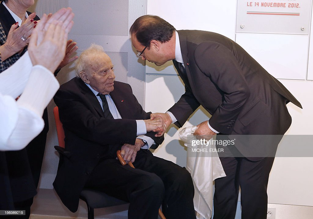 France's President Francois Hollande (R) shakes hands with 1965 Nobel Prize winner in Medicine, Professor Francois Jacob during the inauguration of the new department of the Emerging diseases named after Francois Jacob , on November 14, 2012 at the Pastor institute in Paris.