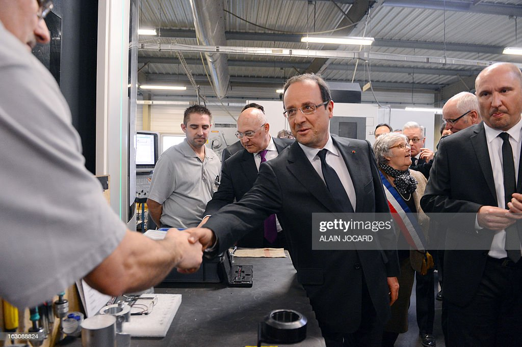 France's President Francois Hollande (C) shakes hands with an employee while visiting a precision tooling store in Blois, on March 4, 2013. POOL