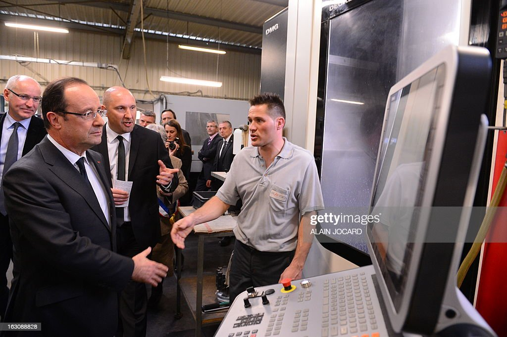France's President Francois Hollande (L) shakes hands with an employee while visiting a precision tooling store in Blois, on March 4, 2013. POOL