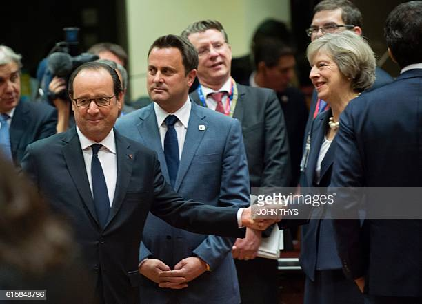 France's President Francois Hollande shakes hands with Britain's Prime minister Theresa May as Luxembourg's Prime minister Xavier Bettel looks on...