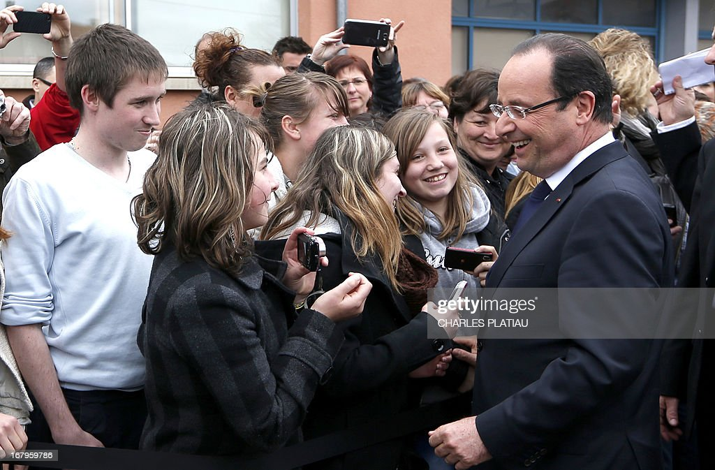 France's President Francois Hollande (R) shakes hands with supporters after visiting a leather goods maker during a one-day visit focused on employment in rural areas in Avoudrey, eastern France, on May 3, 2013. POOL AFP PHOTO CHARLES PLATIAU