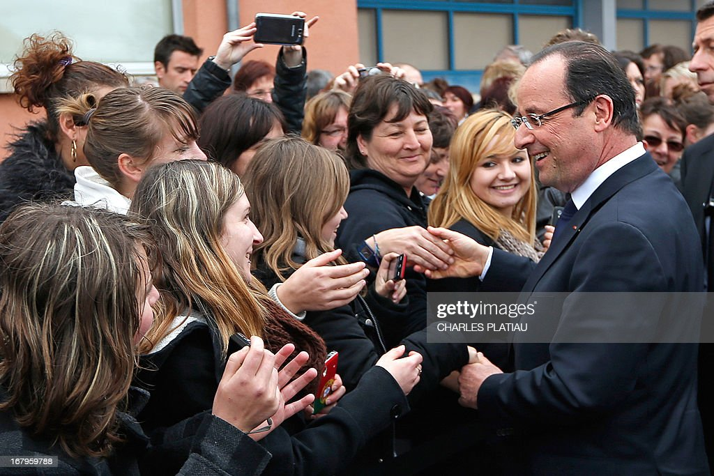 France's President Francois Hollande (R) shakes hands with supporters after visiting a leather goods maker during a one-day visit focused on employment in rural areas in Avoudrey, eastern France, on May 3, 2013. POOL