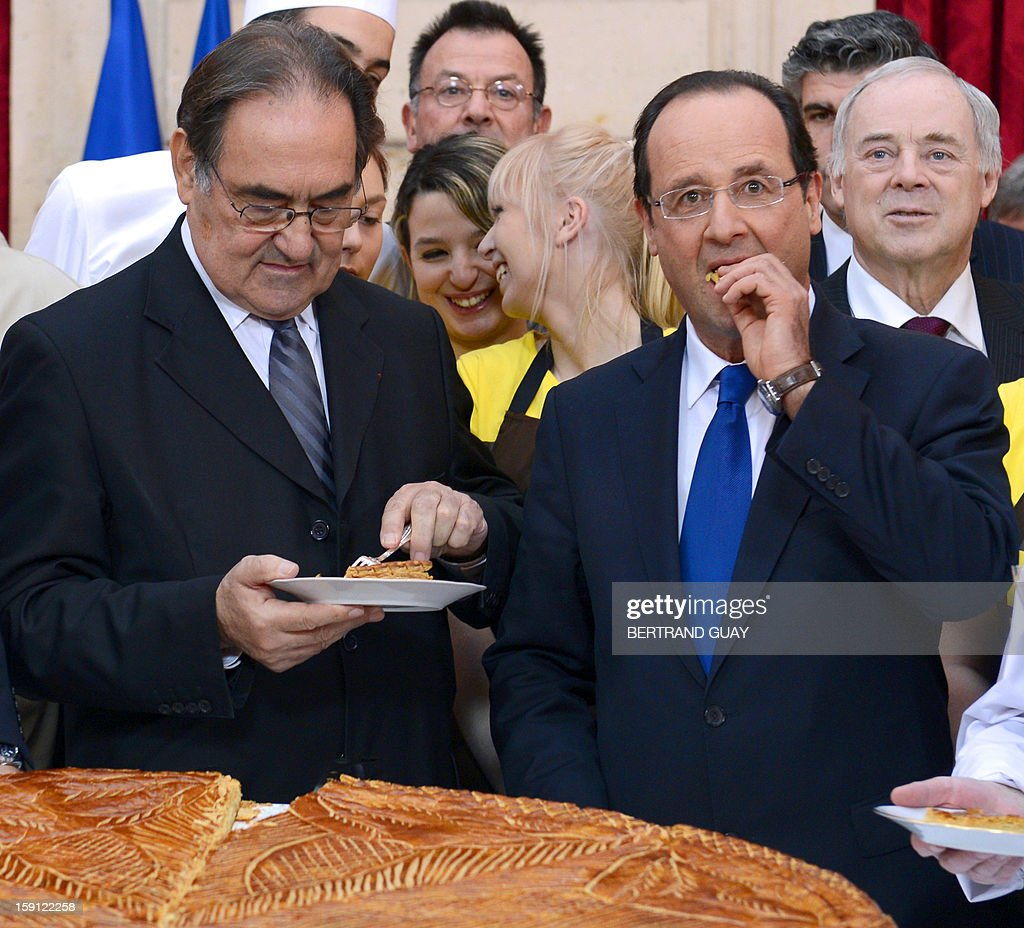 France's President Francois Hollande (R) shares a giant traditional Epiphany cake (galette des rois) next to the president of French bakeries National Confederation Jean-Pierre Crouzet on January 8...