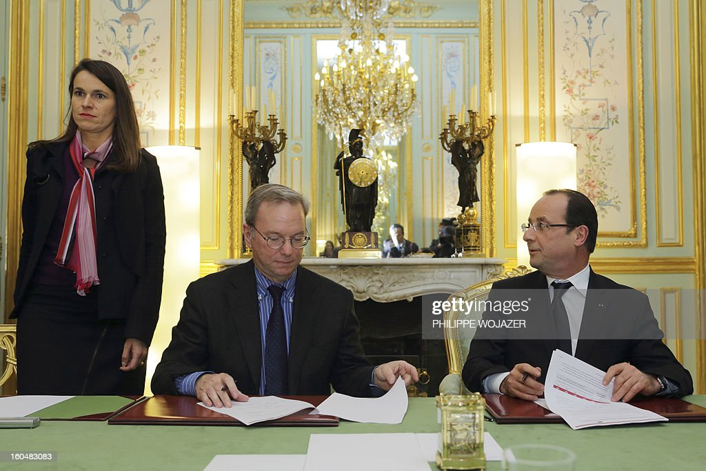 France's President Francois Hollande (R) signs an agreement with Google Executive Chairman Eric Schmidt (C), flanked by France's Culture Minister Aurelie Filippetti (L), at the Elysee Presidential Palace on February 1, 2013 in Paris. AFP PHOTO / POOL / PHILIPPE WOJAZER