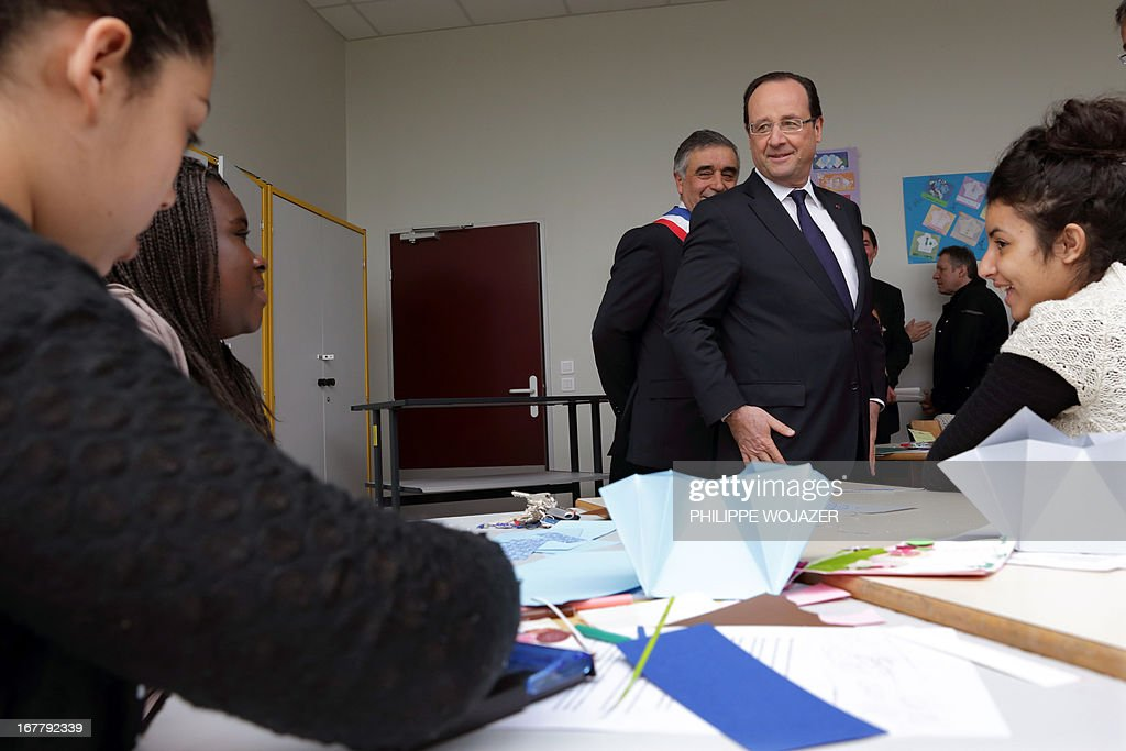 France's President Francois Hollande (C) speaks to pupils in a classroom during a visit focused on the youth employment on April 30, 2013 in a school in Les Mureaux, a Paris' suburb. AFP PHOTO POOL PHILIPPE WOJAZER