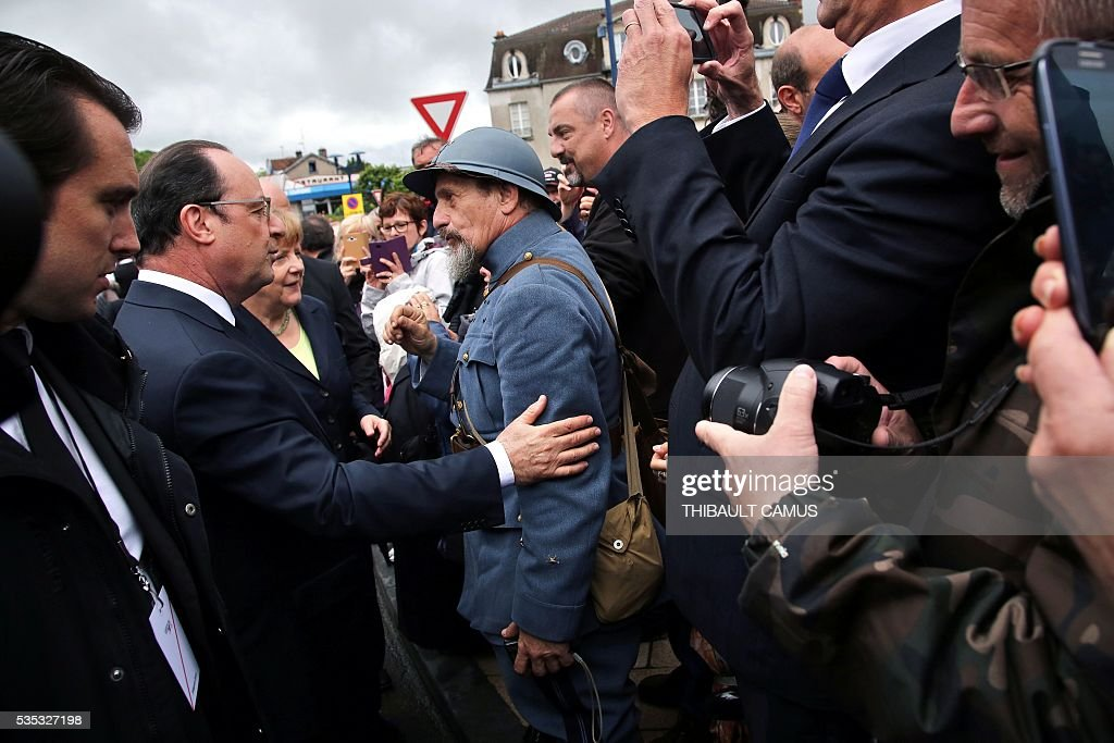 France's President Francois Hollande (L) speaks with a history reenactor dressed as a World War I French soldier during a remembrance ceremony to mark the centenary of the battle of Verdun, on May 29, 2016, in Verdun, northeastern France. The battle of Verdun, in 1916, was one of the bloodiest episodes of World War I. The offensive which lasted 300 days claimed more than 300,000 lives. / AFP / POOL / Thibault Camus