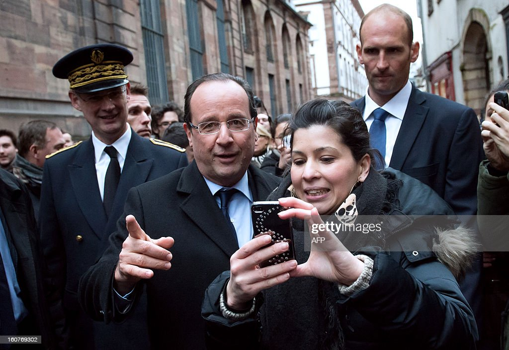 France's President Francois Hollande (C) speaks with a person in front of the town hall of the eastern French city of Strasbourg on February 5, 2013. Hollande said today that he was ready to compromise on the EU's trillion-euro 2014-20 budget but warned that the spending cuts some members want must not undercut fragile growth. At left, Bas-Rhin prefect Stephane Bouillon. AFP PHOTO BERTRAND LANGLOIS