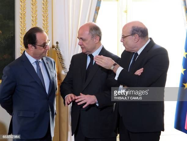 France's President Francois Hollande speaks with French Interior Minister Bruno Le Roux and French Secretary of State for Development and...
