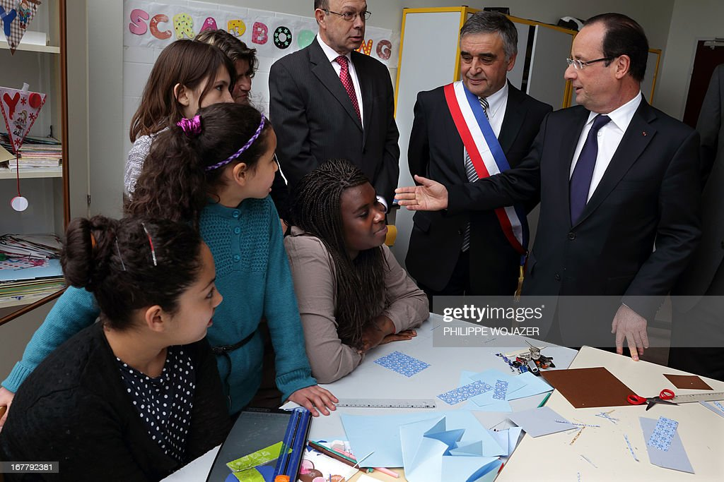 France's President Francois Hollande (R) speaks with pupils in a classroom beside the mayor of Les Mureaux Francois Garay (2ndR) during a visit focused on the youth employment on April 30, 2013 in a shool in Les Mureaux, a Paris' suburb.