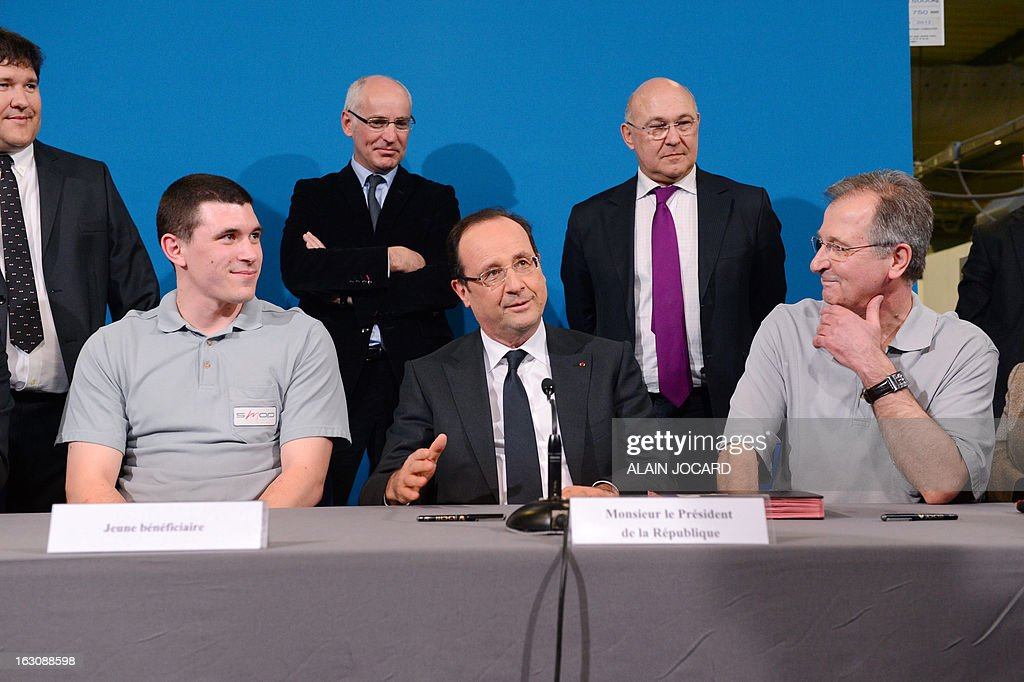 France's President Francois Hollande (C) takes part in a ceremony to sign new apprentice contracts in Blois, on March 4, 2013.