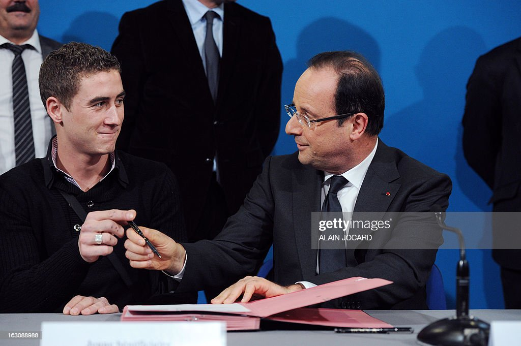 France's President Francois Hollande (R) takes part in a ceremony to sign new apprentice contracts with a youth beneficiary in Blois, on March 4, 2013.