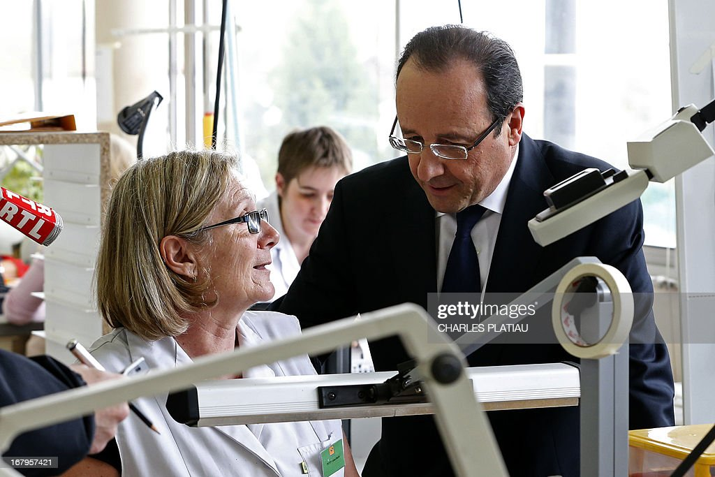 France's President Francois Hollande (R) talks to an employee as he visits a leather goods maker during a one-day visit focused on employment in rural areas in Avoudrey, eastern France, on May 3, 2013. POOL