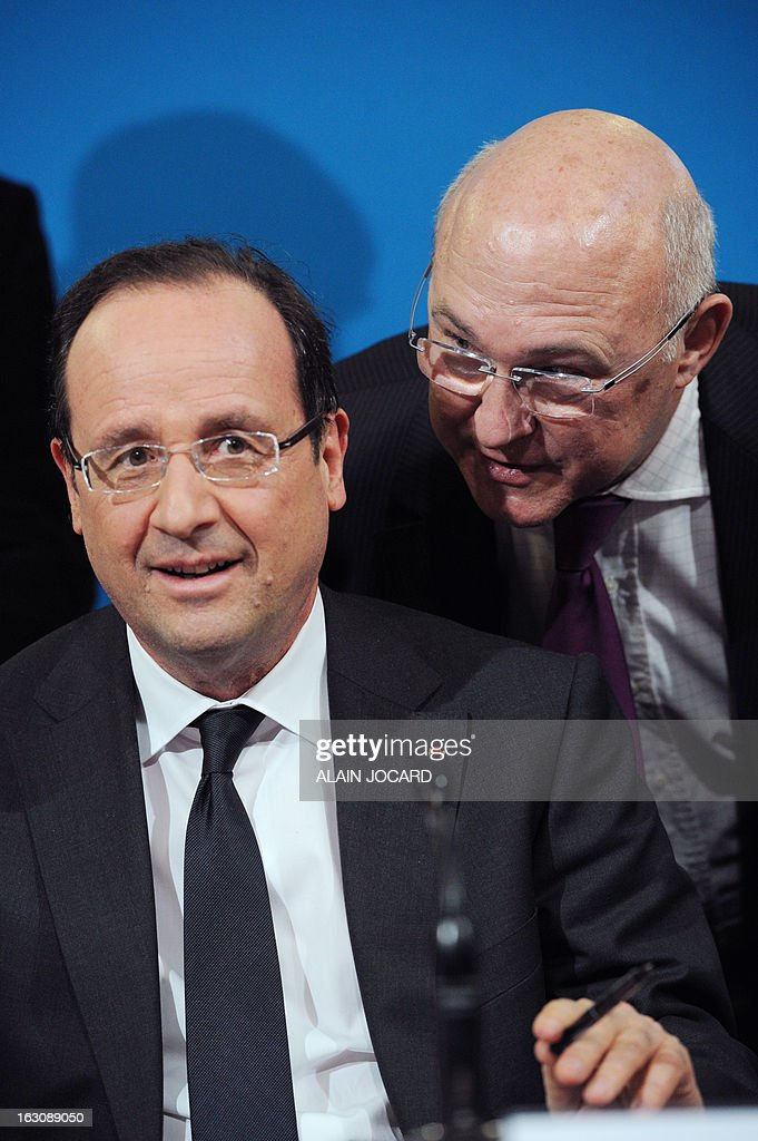 France's President Francois Hollande (L) talks to France's Labour minister Michel Sapin during ceremony to sign new apprentice contracts in Blois, on March 4, 2013.