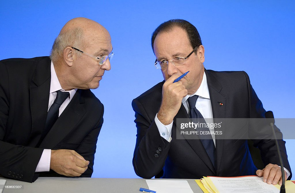 France's president Francois Hollande (R) talks with French Labour, Employment and Social Dialogue Michel Sapin (L) before a meeting with trainees at the GRETA (French public centers for trainees) during a visit focusing on employment and adult professional training on October 8, 2013, in Mably near Roanne, central France.