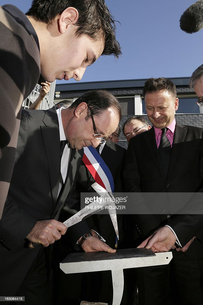 France's President Francois Hollande uses specialized tools to split a piece of slate used for roofing at an apprentice training centre in Blois, on March 4, 2013. POOL