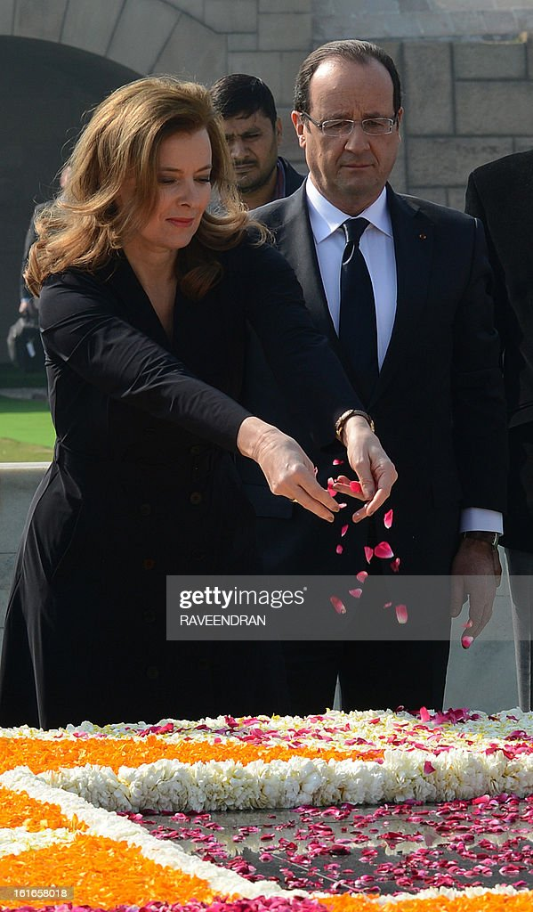 France's President Francois Hollande (R) watches his partner Valerie Trierweiler (L) spread flower petals at a ceremony at Rajghat, the memorial of India's founding father Mahatma Gandhi in New Delhi on February 14, 2013. French President Francois Hollande embarked on a fresh push to clinch a USD 12-billion sale of Rafale fighter jets as he held talks in India on his first visit to Asia since taking office. The Socialist president was accompanied by a high-powered delegation of five ministers including Foreign Minister Laurent Fabius and Defence Minister Jean-Yves Le Drian and the chiefs of more than 60 top French companies.