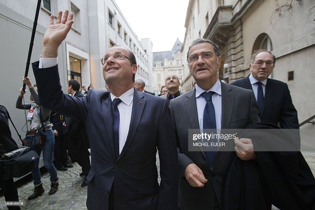 France's President Francois Hollande (L) waves as he walks with winner of the 2012 Nobel Prize in physics, Serge Haroche of France (R) at the College de France (an elite research institution) in Paris, on February 4, 2013. French President Francois Hollande honored by his visits Serge Haroche for his 2012 Nobel prize in physics.