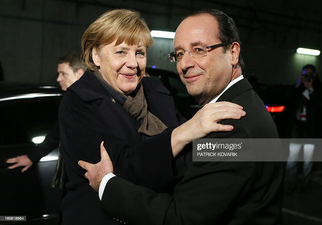 France's President Francois Hollande welcomes German Chancellor Angela Merkel at the Stade de France in Saint-Denis, near Paris, before attending a friendly international football match between France and Germany on February 6, 2013. The match marks the 50th anniversary of the establishment of the Elysee Treaty, which paved the way for friendly relations between two countries that had previously endured a long and bitter rivalry.