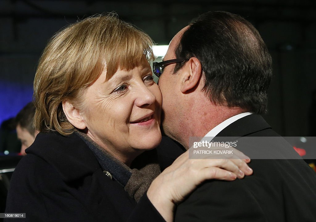 France's President Francois Hollande welcomes German Chancellor Angela Merkel at the Stade de France in Saint-Denis, near Paris, before attending a friendly international football match between France and Germany on February 6, 2013. The match marks the 50th anniversary of the establishment of the Elysee Treaty, which paved the way for friendly relations between two countries that had previously endured a long and bitter rivalry. AFP PHOTO / POOL / PATRICK KOVARIK