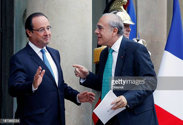 France's President Francois Hollande welcomes Organisation for Economic Cooperation and Development Secretary General Jose Angel Gurria prior to a...