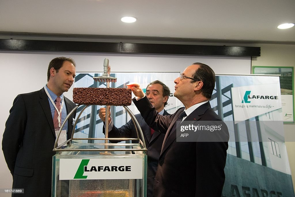 France's President Francois Hollande (R), with Lafarge CEO Bruno Lafont (C), visits a Lafarge construction development lab in Mumbai on February 15, 2013 during a two-day state visit to India. French President Francois Hollande wrapped up his two-day trip to India on Friday with a call for more investment and trade between the countries as he met with business leaders.