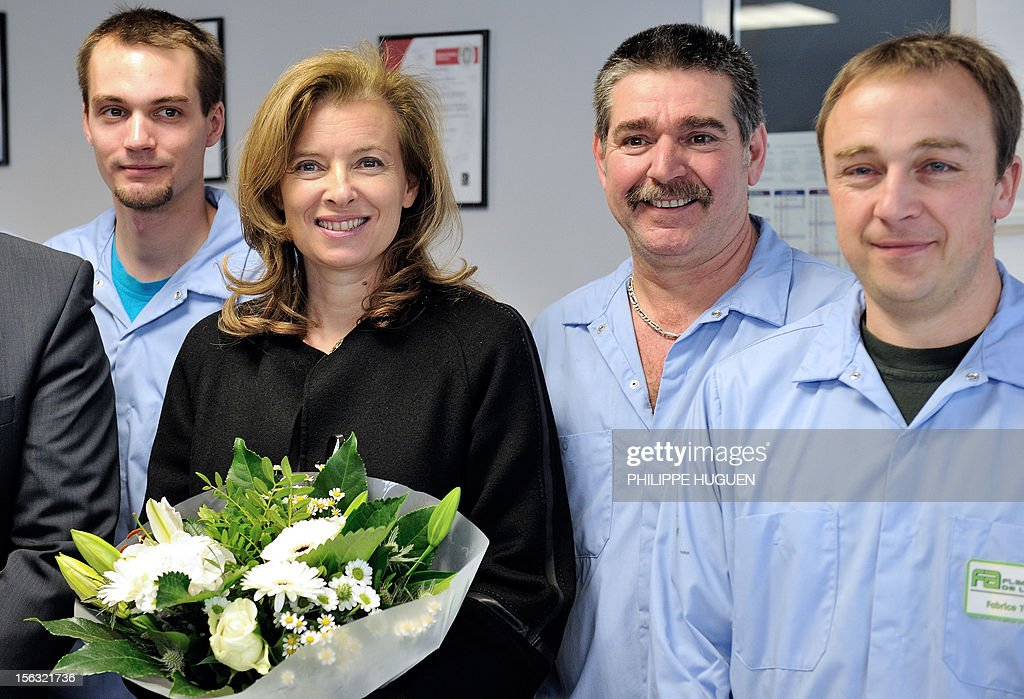 France's President Francois Hollande's companion Valerie Trierweiler, holds a bunch a flowers as she poses with employees as she visits a flask making factory, 'flaconnage de l'Artois' on November 13, 2012 in Lapugnoy, eastern France. AFP PHOTO / PHILIPPE HUGUEN