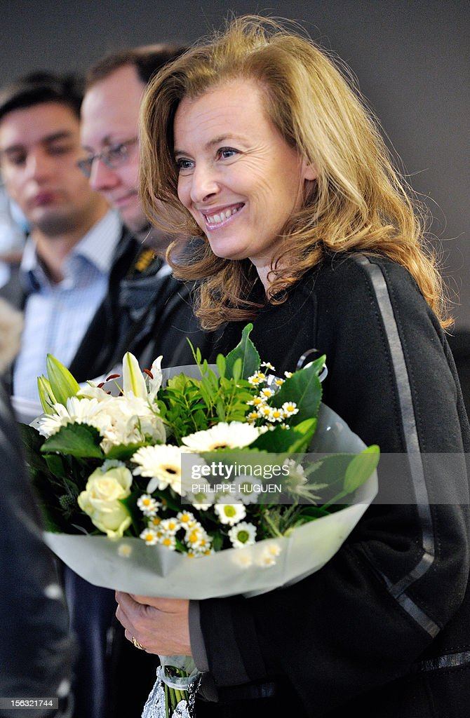 France's President Francois Hollande's companion Valerie Trierweiler, holds a bunch of flowers as she visits a flask making factory, 'flaconnage de l'Artois' on November 13, 2012 in Lapugnoy, eastern France.