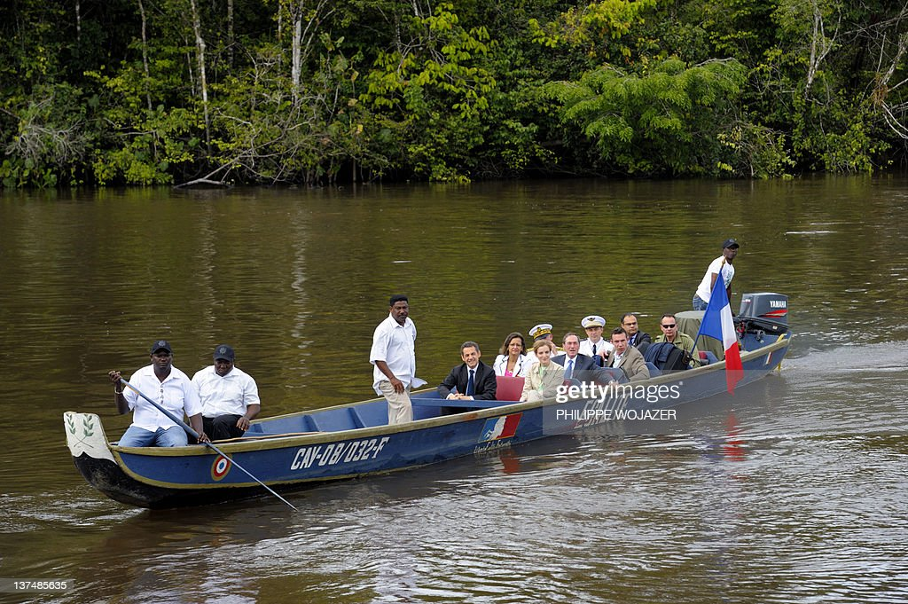 France's President Nicolas Sarkozy (C) and members of the government sit in a pirogue sailing on the Maroni river on their way to Talwen, French Guiana, prior to a meeting with local authorities and inhabitants, on January 21, 2012.