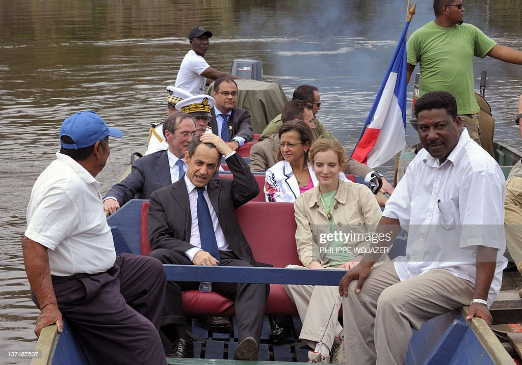 France's President Nicolas Sarkozy (2ndL), Interior Minister Claude Gueant (L),Overseas Minister Marie-Luce Penchard (3rdL), and Environment and Transport Minister Nathalie Kosciusko-Morizet (4thL) sit in a pirogue sailing on the Maroni river on their way to Talwen, French Guiana, prior to a meeting with local authorities and inhabitants, on January 21, 2012.