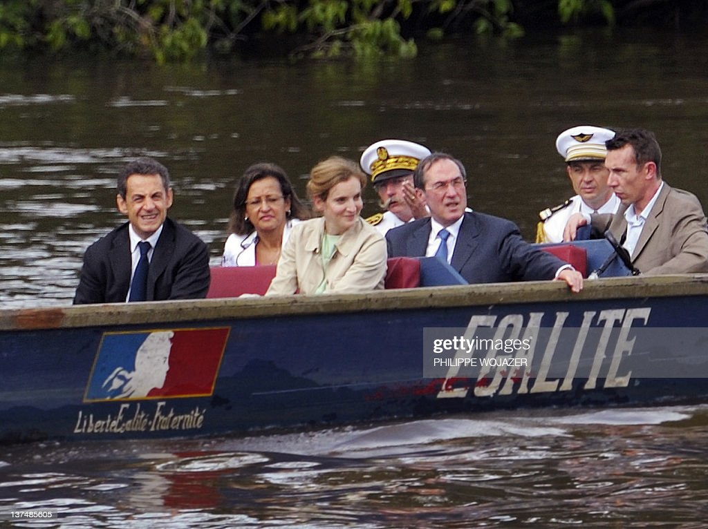 France's President Nicolas Sarkozy (L), Overseas Minister Marie-Luce Penchard (2ndL), Environment and Transport Minister Nathalie Kosciusko-Morizet (3rdL) and Interior Minister Claude Gueant (5thL) sit in a pirogue sailing on the Maroni river on their way to Talwen, French Guiana, prior to a meeting with local authorities and inhabitants, on January 21, 2012. AFP PHOTO POOL PHILIPPE WOJAZER