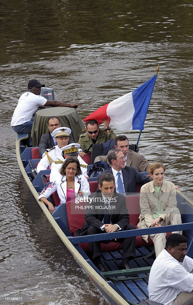 France's President Nicolas Sarkozy (2ndL), Overseas Minister Marie-Luce Penchard (L), Environment and Transport Minister Nathalie Kosciusko-Morizet (4thL) and Interior Minister Claude Gueant (3rdL) sit in a pirogue sailing on the Maroni river on their way to Talwen, French Guiana, prior to a meeting with local authorities and inhabitants, on January 21, 2012. AFP PHOTO POOL PHILIPPE WOJAZER