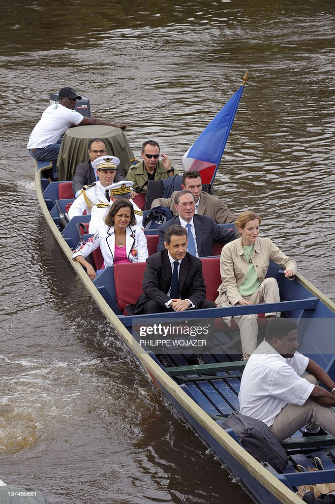 France's President Nicolas Sarkozy (2ndL), Overseas Minister Marie-Luce Penchard (L), Environment and Transport Minister Nathalie Kosciusko-Morizet (4thL) and Interior Minister Claude Gueant (3rdL) sit in a pirogue sailing on the Maroni river on their way to Talwen, French Guiana, prior to a meeting with local authorities and inhabitants, on January 21, 2012.