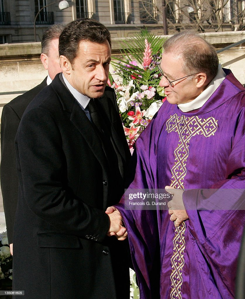 France's president Nicolas Sarkozy shakes hand with father Daniel Ponsard as he arrives at the Madeleine Church in Paris to attend French crooner...