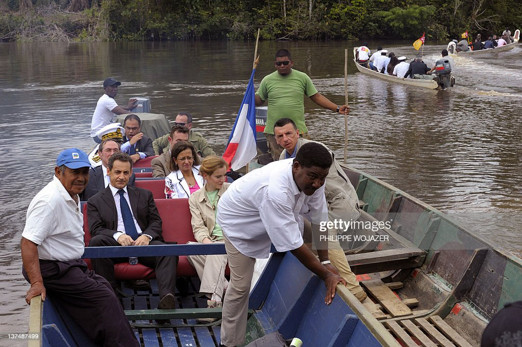 France's President Nicolas Sarkozy (L) sits in a pirogue sailing on the Maroni river on their way to Talwen, French Guiana, prior to a meeting with local authorities and inhabitants, on January 21, 2012.