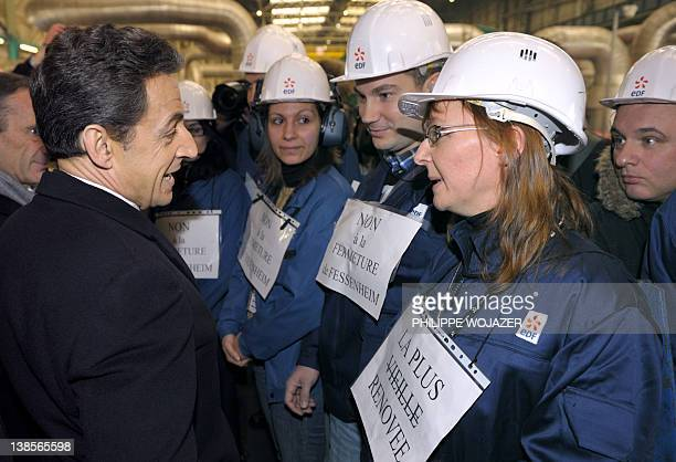 France's President Nicolas Sarkozy speaks to workers holding posters reading 'Don't close Fessenheim' as he visits the nuclear powerplant in...