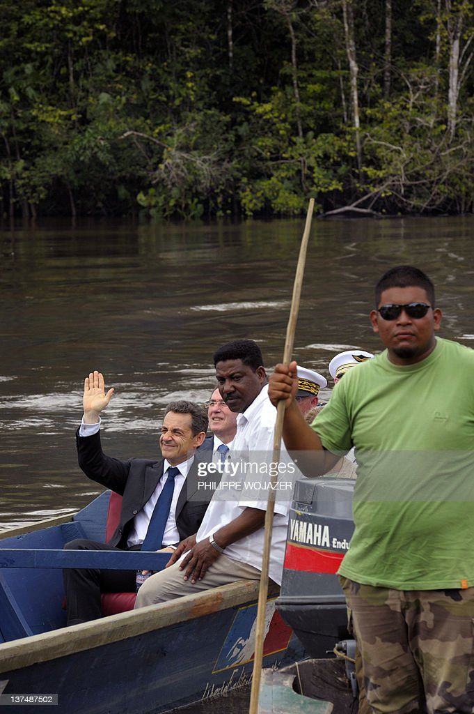 France's President Nicolas Sarkozy (L) waves sitting in a pirogue sailing on the Maroni river as they arrive in Talwen, French Guiana, prior to a meeting with local authorities and inhabitants, on January 21, 2012.