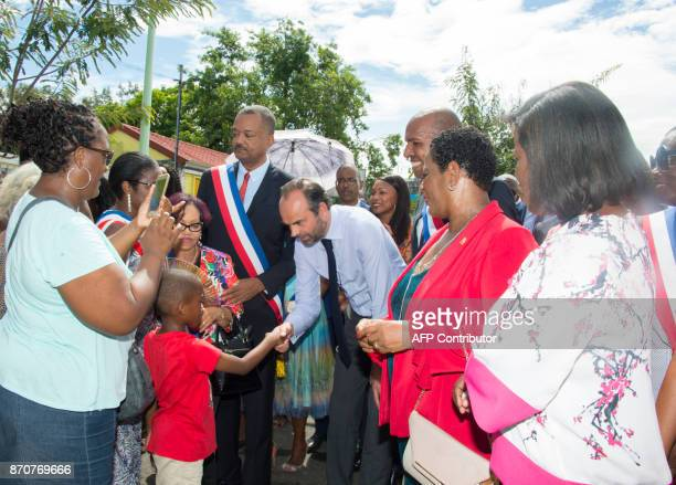 France's Prime Minister Edouard Philippe flanked by mayor of Les Abymes Eric Jalton speaks with a child in Les Abymes on the French Caribbean Island...