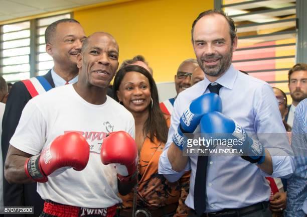 France's Prime Minister Edouard Philippe flanked by Thai boxe Champion Bruno Brendan wears boxing gloves during a visit at Emmanuel Albon Centre at...