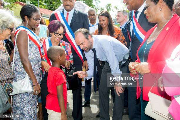 France's Prime Minister Edouard Philippe speaks with a child in Les Abymes on the French Caribbean Island of Guadeloupe on November 5 2017 during a...