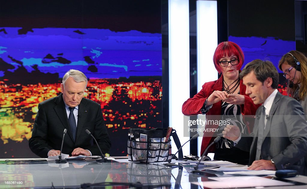 France's Prime minister Jean-Marc Ayrault (L) gets ready to take part in the broadcast news of France 2 TV channel on April 2, 2013. France's ex-budget minister Jerome Cahuzac was charged today in a tax fraud probe after he admitted having a foreign bank account, dealing a fresh blow to President Francois Hollande's embattled government.