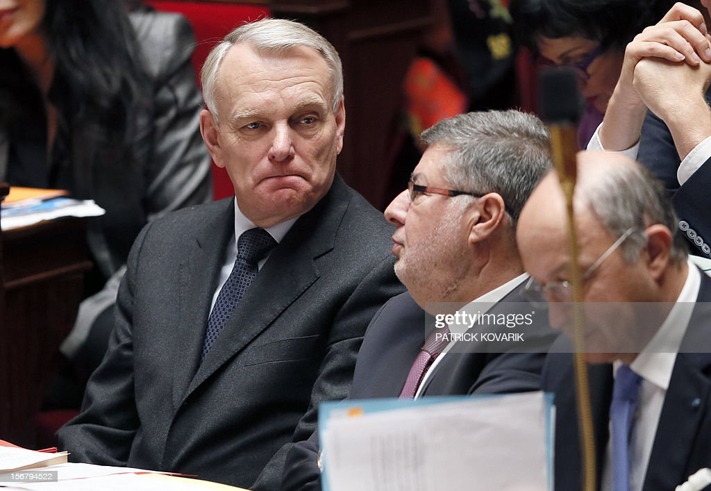 France's Prime minister Jean-Marc Ayrault looks on next to Junior minister for Parliament relation Alain Vidalies during the weekly session of questions at the National Assembly on November 21, 2012 in Paris. AFP PHOTO / PATRICK KOVARIK