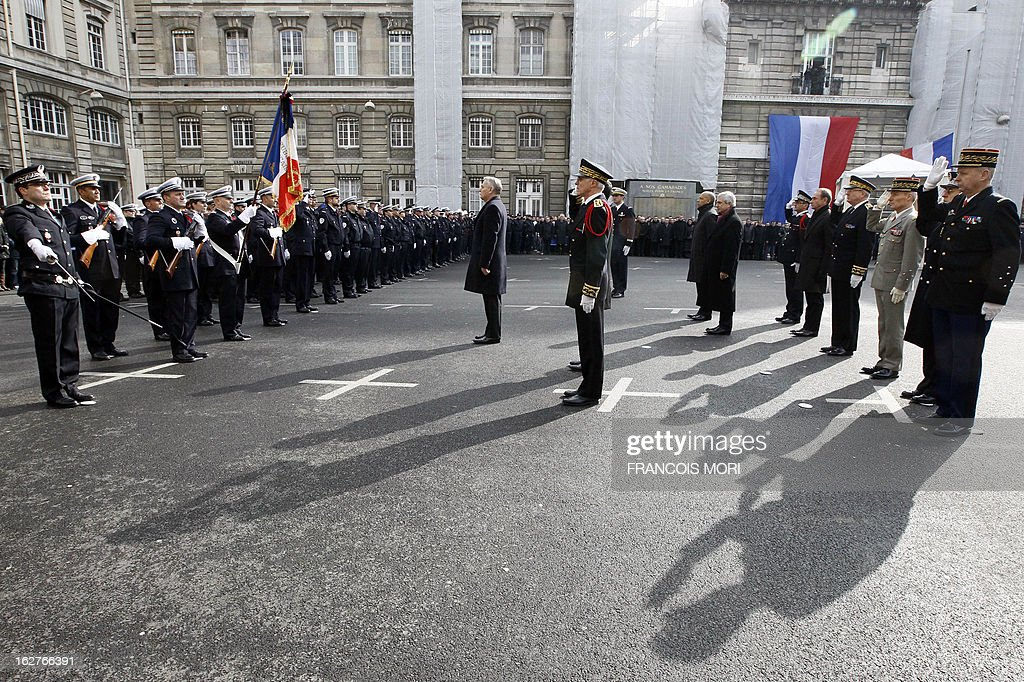 France's Prime Minister Jean-Marc Ayrault (C) pays homage in the yard of the Paris police prefecture on February 26, 2013 during a ceremony for the two slain policemen in Paris. An alleged drunk driver killed the two Paris police officers after slamming his black Land Rover into their cruiser during a high-speed chase on the ring road around Paris.