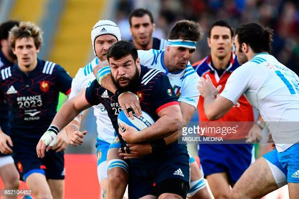 France's prop Rabah Slimani is tackled by Italy's flanker Dries van Schalkwyk during the International Six Nations rugby union match Italy vs France...