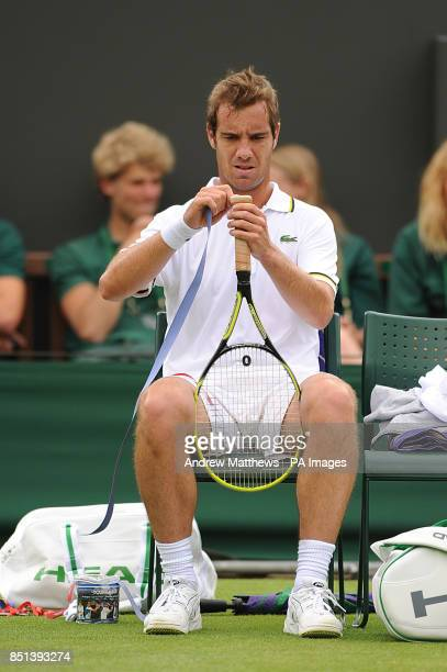 France's Richard Gasquet restraps his raquet in between games against Spain's Marcel Granollers during day two of the Wimbledon Championships at The...