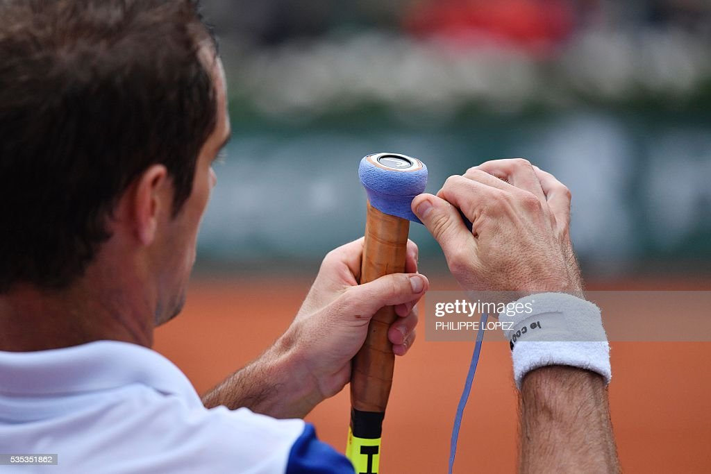 France's Richard Gasquet rewraps the tennis grip on his racket during his men's fourth round match against Japan's Kei Nishikori at the Roland Garros 2016 French Tennis Open in Paris on May 29, 2016. / AFP / PHILIPPE