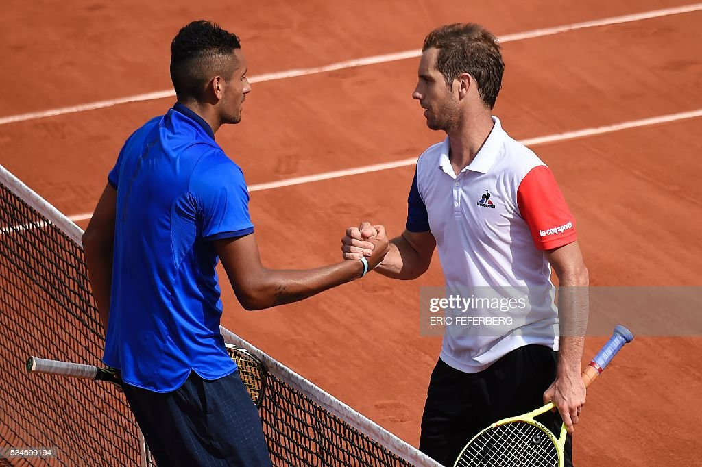 France's Richard Gasquet (R) shakes hands with Australia's Nick Kyrgios after winning their men's third round match at the Roland Garros 2016 French Tennis Open in Paris on May 27, 2016. / AFP / Eric FEFERBERG